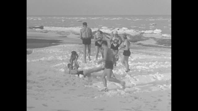"""chicago swimmers find zero weather ideal for plunge into lake michigan"""" / vs men and women in bathing suits have snowball fight on shore of lake... - 水泳用浮き輪点の映像素材/bロール"""