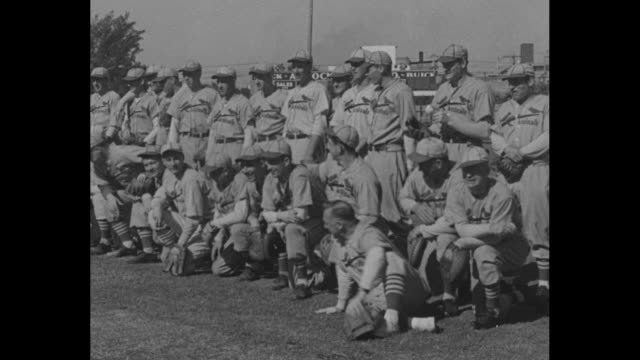 St Louis Cards Train For Opener / Title St Petersburg Fla superimposed over St Louis Cardinals team posing for photo opportunity / players run onto...