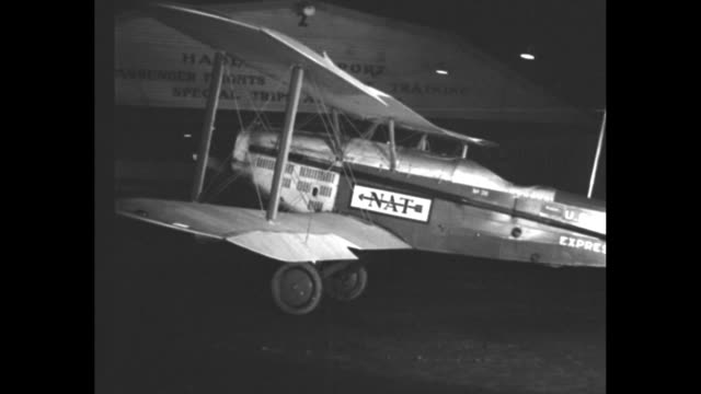 """start 32-hour coast air mail, hadley field, nj - night flying speeds up service across country"" / night view of biplane being towed by tail on... - united states postal service stock videos & royalty-free footage"