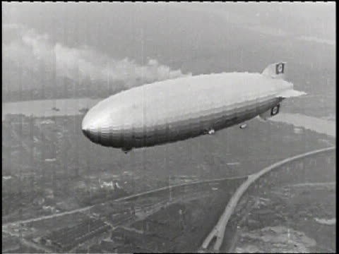 A title card stating Actual zeppelin crash / A zeppelin files though the air over a city /