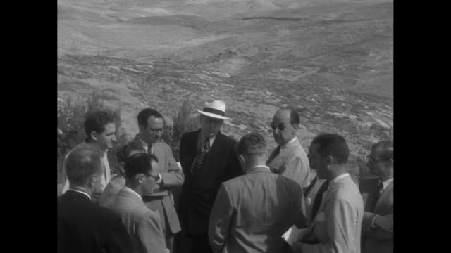 vidéos et rushes de stevenson visits israel on global tour superimposed over stevenson shaking hands / stevenson standing with group of men on hilltop overlooking desert... - adlai stevenson