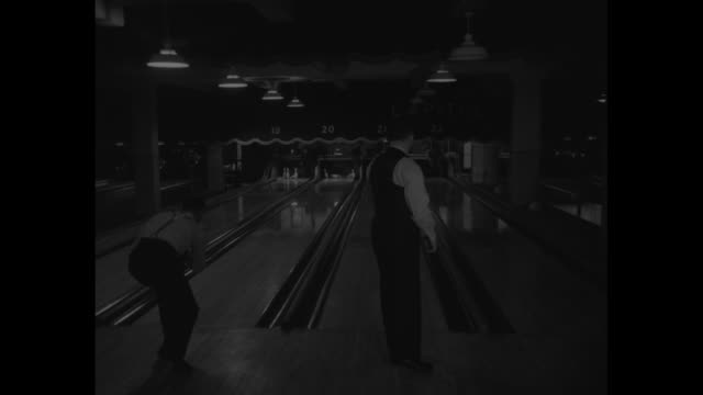 strike $5000 bowling contest starts / bowling ball knocking down bowling pins for a strike / side view of bowlers rolling balls in unison down... - ボーリング場点の映像素材/bロール