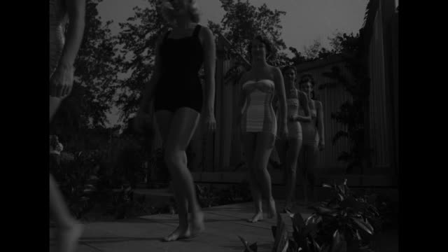 "stockvideo's en b-roll-footage met ""stripes star in '51 swim styles"" superimposed over models in striped swimsuits / vs models in striped swimsuits by pool show for audience of women... - beverly hills californië"