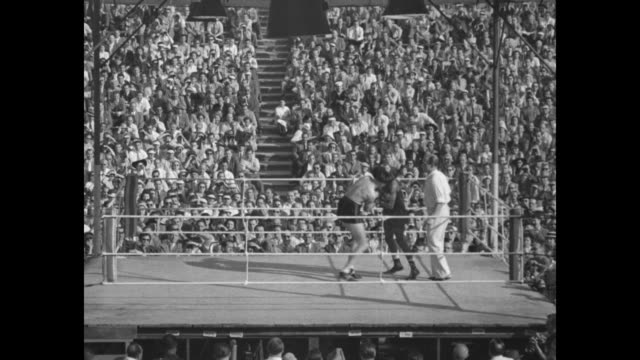 sugar ray fight starts berlin riot over footage in outdoor boxing ring as sugar ray robinson knocks gerhard hecht down and referee begins eight count... - shock tactics stock videos and b-roll footage
