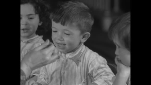 """""""'sunshine' in the form of cod liver oil"""" / three shots of teacher using spoon to feed cod liver oil to children sitting at table / title page """"where... - spielzeughaus stock-videos und b-roll-filmmaterial"""