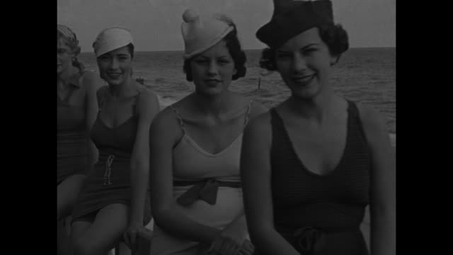 """""""surf girls show styles, miami beach - while the north shivers, florida holds first beach show of season! bathing girls display newest modes of 1934... - sun hat stock videos & royalty-free footage"""