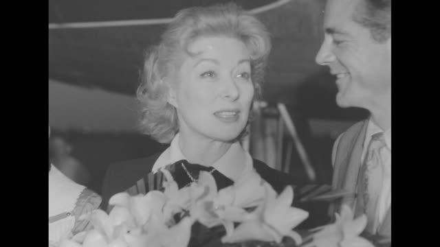 vidéos et rushes de texas premiere for 'strange lady in town' superimposed over night shot of film star greer garson deplaning in austin tx and accepting a bouquet of... - actrice