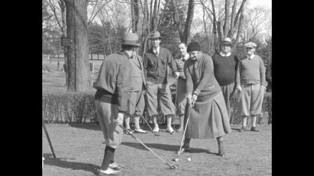 the baroness finds golf is topping / a golf pro tells baroness helene von hindenburg how to grip her iron golf club sot baroness keep your eye on the... - ヒンデンブルク号点の映像素材/bロール
