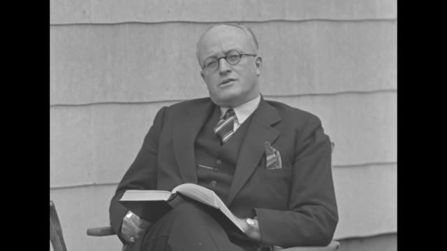 """the british public��the final judges"" / title: ""hugh walpole "" superimposed over author walpole, seated outdoors with a book on his lap, as sot he... - 1930 video stock e b–roll"