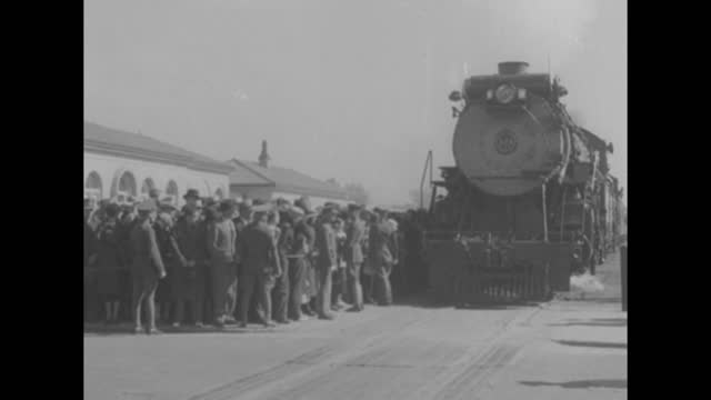 """""""the camera reporter"""" superimposed over man behind motion picture camera turning / front view of presidential train coming to a stop, as crowds wait... - wyoming stock videos & royalty-free footage"""
