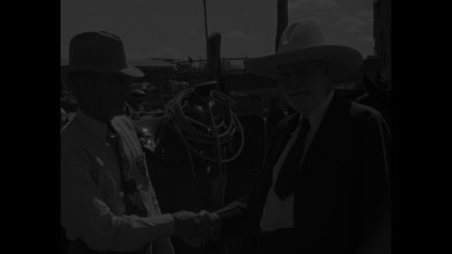 The Gang's All Here at Cowboy Reunion / CU tilt up cowboy procession into town / CU tilt up cowgirl procession into town / CU cowgirl W Fay Cowden on...
