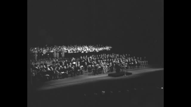 vídeos y material grabado en eventos de stock de the grand chorus / vs radio city music hall chorus singing inside hall during service noting the beginning of the holy year notables sitting on stage... - radio city music hall