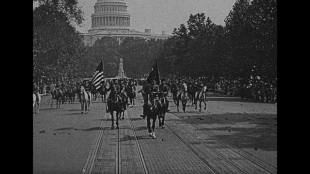 Title card The Nation's Capital welcomes General Pershing and the First Division / Pershing approaches riding a horse with United States Capitol dome...