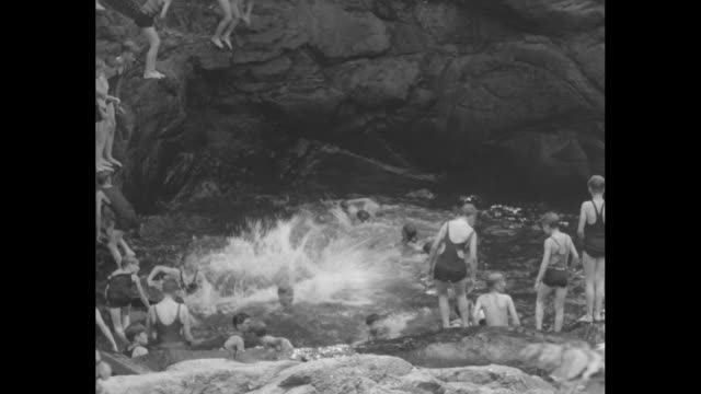 the ol' swimming hole / boys on big rocks hurriedly taking off clothes they start jumping in swimming hole / ms boys on rocks one is black no... - orphan stock videos & royalty-free footage