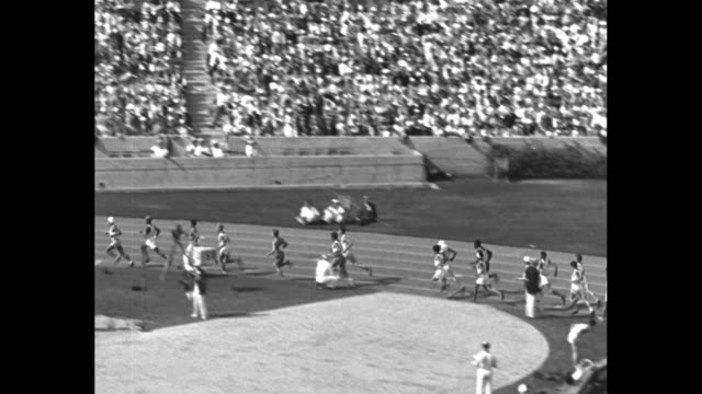 the olympic classic the marathon / field of several dozen runners start race pan as they round the track / field level as runners approach on front... - 1932 stock videos & royalty-free footage