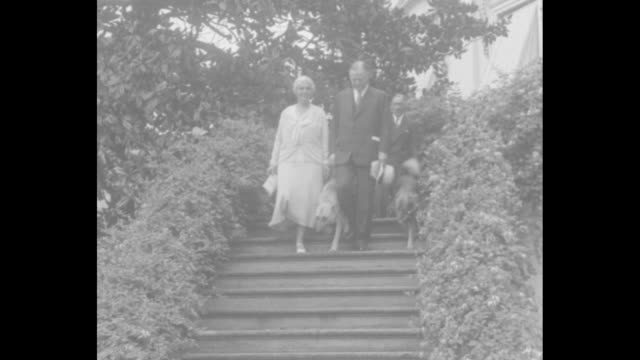 the president and mrs hoover pose for official photographs … / pres herbert hoover and first lady lou hoover walking together outdoors down steps... - herbert hoover us president stock videos & royalty-free footage