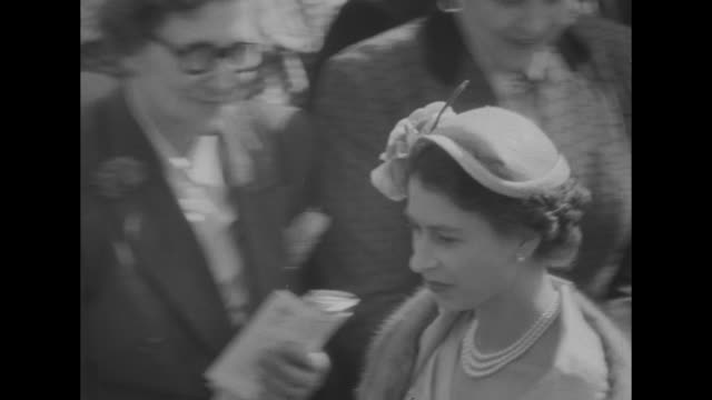 stockvideo's en b-roll-footage met the royal ascot superimposed over pan of racetrack / two couples men wearing top hats walk right / large crowd some under trees / queen elizabeth the... - hoed
