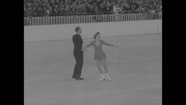 'THE WINTER OLYMPICS' superimposed over Canadian pairs figure skaters Norris Bowden and Frances Dafoe performing their routine / MLS crowded section...