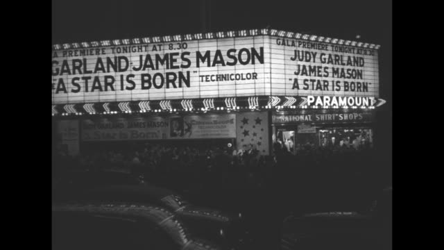 Throngs Storm N Y Showing of 'Star is Born' superimposed over night shot of excited fans behind a police line barricade / night LS Times Square with...