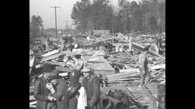 """stockvideo's en b-roll-footage met """"tornado - 2-minute twister death toll is 25"""" / a few men look through pile of rubble, wood and other debris, three men in foreground, one lighting a... - city of neighbors: give once for all film title"""