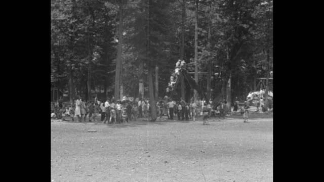 """""""treat city kids to camp thrills, sharon, mass - 4000 poor children romp and play as salvation army guests"""" / scores of children on campground under... - wippe stock-videos und b-roll-filmmaterial"""
