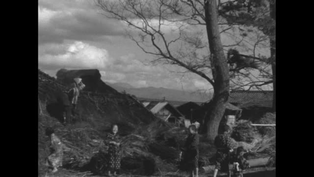 typhoon's toll japanese dig out of ruins after storm destroys village / japanese villagers go through possessions after typhoon hit village mount... - 1930~1939年点の映像素材/bロール