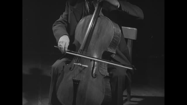 "vidéos et rushes de ""un nuovo mezzo strumentale: il clavioline"" / vo in italian language throughout / 3 men in front on a grand piano / they attach electric keyboard,... - violoncelle"