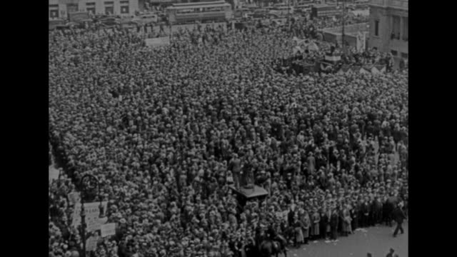 'UNION SQUARE MOSCOW IDAHO Pipsqueak sees red' / high angle views of huge crowds gathered in city center some carrying large signs / CU character...