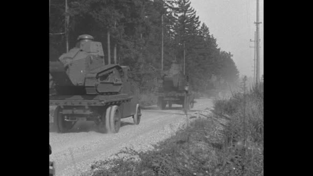 'US Tanks Tune Up for Action Ft Lewis Wash Third Tank Company stages own war in speedy workout' / VS convoy of trucks bearing small tanks approaches...