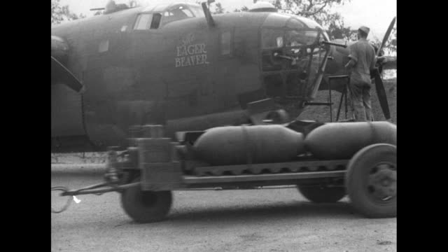 "vídeos y material grabado en eventos de stock de in action"" / 1000 bombs are delivered to consolidated b-24 liberator with ""eager beaver"" painted on side / crew of the plane / vs nose art: ""seafood... - explosivo"