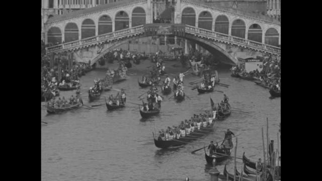 """picturesque pageant of gondolas on famed grand canal thrills italian ruler"""" / high angle of several gondolas proceeding down grand canal toward... - regatta stock-videos und b-roll-filmmaterial"""