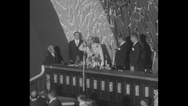 Title card Venezuela Inaugurates a President / constitutional assembly standing and applauding as Marcos Perez Jimenez enters assembly waving / Perez...