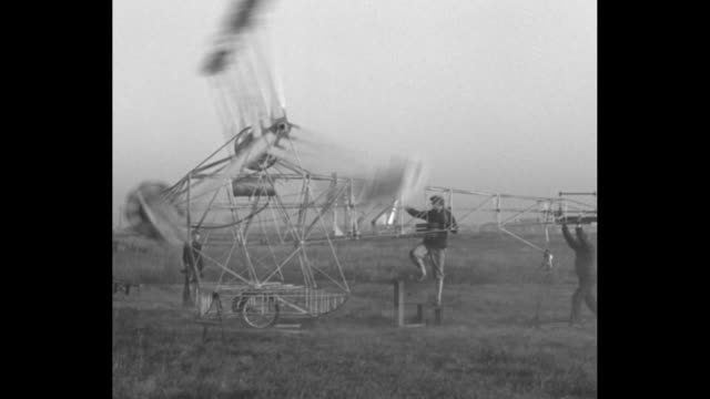 Warms up new Thresher plane Chicago Ill Inventor Nemeth tunes motor on odd helicopter flying machine / VS A skeleton fuselage with vertical blades...