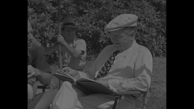 wc fields acts again / cu fields sitting in chair / director mitchell leisen walks over to fields from rest of film crew sits in folding director's... - ディレクター点の映像素材/bロール