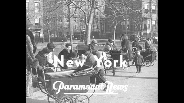 """""""weather goes haywire - ask californians!"""" / title: """"new york"""" superimposed over women with baby carriages sit on park bench and children play /... - altalena video stock e b–roll"""