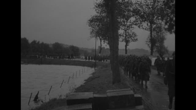 west front flooded moselle hampers troops / ls french infantrymen marching along treelined road in pouring rain in background flooded moselle river... - esercito militare francese video stock e b–roll