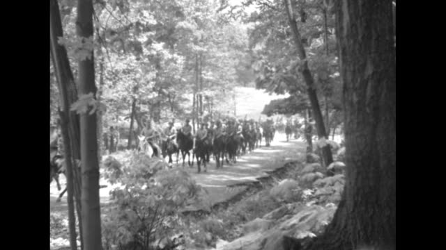 West Point cadets win their spurs / four shots of column of US Military Academy cadets riding horses along trail through woods / four shots of cadets...