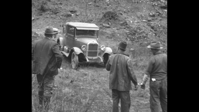 what happens to a car denied a trial by jury / two handcuffed male moonshiners and one prohibition officer stand in foreground with backs to camera... - 禁酒法点の映像素材/bロール
