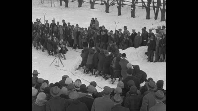 'Where pull really counts' / three shots of two groups of people in the snow in tug of war contest in snow small crowd watching / one group wins by...