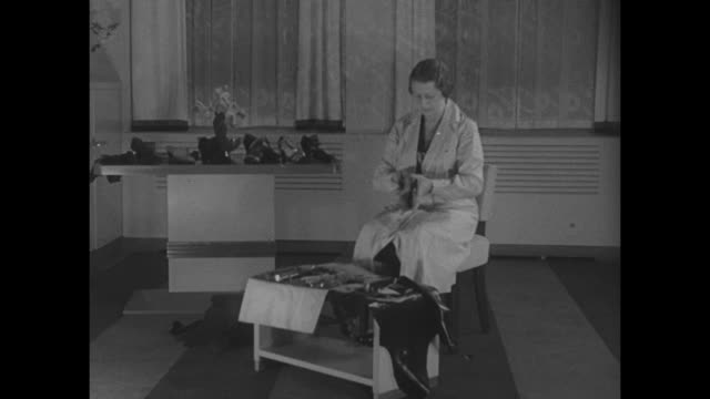 "stockvideo's en b-roll-footage met ""winter shoes, madame? new york - meet the world's only woman shoemaker! mme. julienne of paris, here on a visit, shows how she makes smart shoe... - 1930"