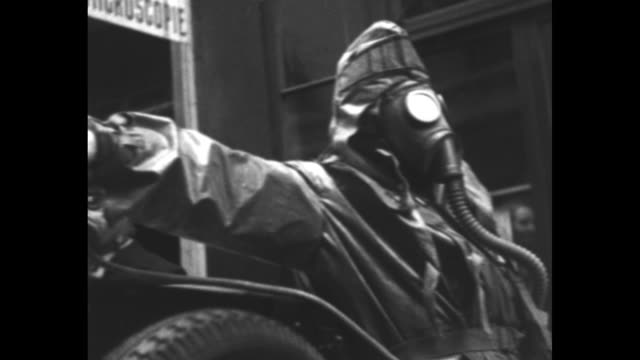 "title card with a gas mask: ""paris, exercises de defense anti-aerienne"" / an official in a shiny helmet and a gas mask looks into an open police call... - sidecar stock videos & royalty-free footage"