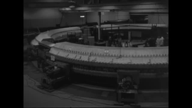 vídeos de stock e filmes b-roll de world's mightiest atom smasher superimposed over electricity flashing on black screen / outdoor sign brookhaven national laboratory / car drives up... - radiação