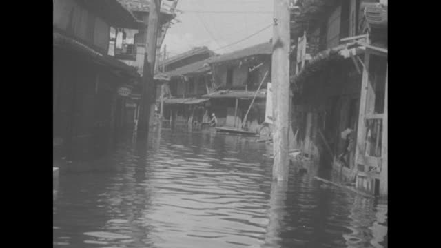 worst postwar typhoon kills 250 in japan superimposed over two people standing in the doorway of a flooded store in tokyo / high angle ls flooded... - 1950~1959年点の映像素材/bロール