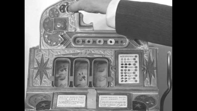 vidéos et rushes de you can't win / pan across room full of slot machines / close shot of man's hand putting coin in machine and pulling lever / man speaking about slot... - machine à sous