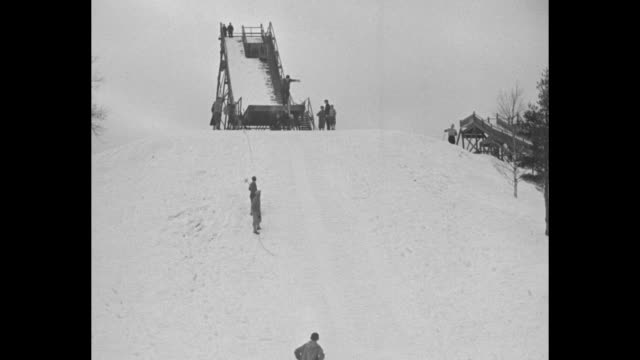 Youngest skiers hit the highspots Lake Placid NY boys from six to twelve learn art of jumping on steep course / VS several young skiers jump from a...