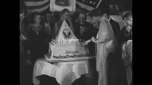 """roosevelt's happiest birthday"" / washington, dc: a pyramidal cake featuring the presidential seal stands on a table, with former first lady edith... - electric chair stock videos & royalty-free footage"