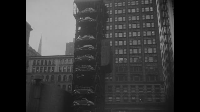 """""""chicago, ill."""" superimposed over bird's-eye shot parking garage with cars on moving levels in midst of parking lot / pan down tower with cars parked... - big wheel stock videos & royalty-free footage"""