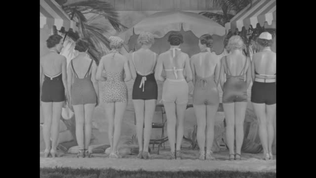 Chicago Ill superimposed over row of models in bathing suits standing with backs to camera models turn around to face camera / models in beachwear in...