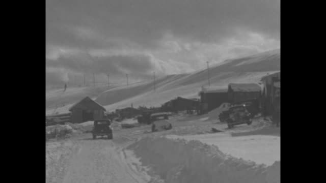 Colorado superimposed over car on snowy farm road / MS two bundled people walk on side of windy snowy hill / Pan car drives on snowy farm road / MS...