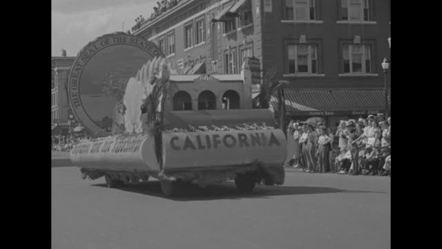 'Colorado' superimposed over exterior of the Denver City and County Building / parade through downtown Denver / float in parade with 'California' on...